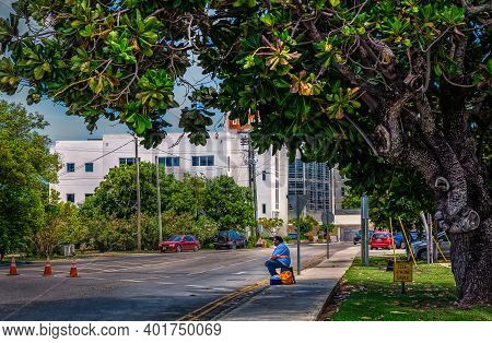 Grand Cayman, Cayman Islands, July 2020, View Of A Man Sitting And Waiting By The Side Of The Road I