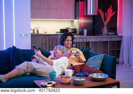 Man Plays On Gaming Console Using Joystick While Woman Using Smart Phone With Gaming App. Millenial
