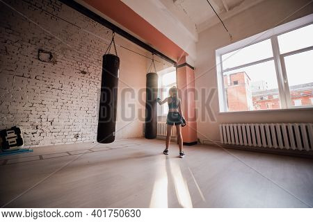 A Pretty Kickboxer Girl Is Preparing For Competitions In The Boxing Hall, Practicing The Technique O