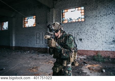 Special Forces Soldier Walking With Aimed Assault Rifle In Destroyed Building.