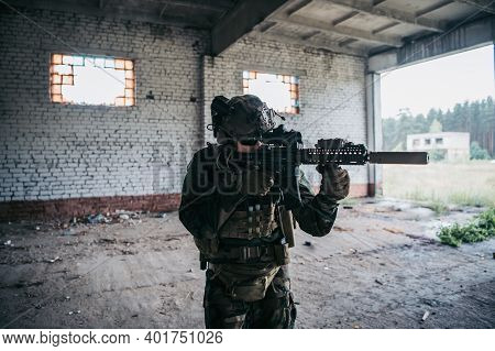 Soldier In Full Us Marsoc Armed With Assault Rifle Run Through The Abandoned Building. Military Clas