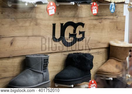 Belgrade, Serbia - December 8 2020: Ugg Logo In Front Of Some Of Their Boots For Sale In A Shop. Ugg