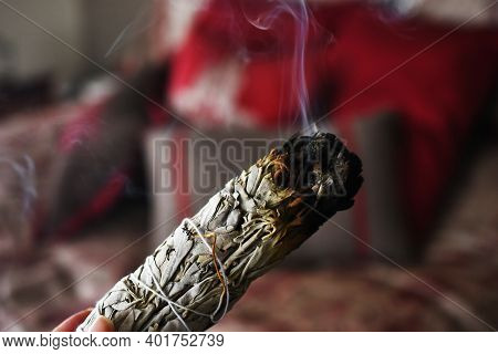 A Close Up Image Of A Burning White Sage Smudge Stick Being Used To Smudge A Room.