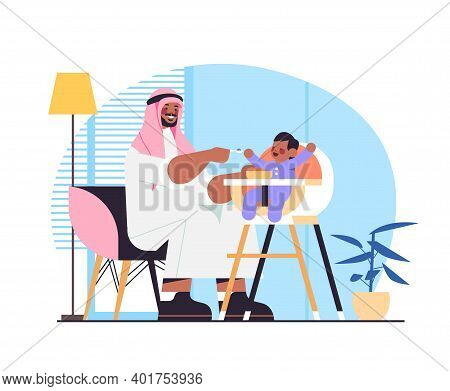 Arab Father Feeding His Little Son On Kids Eating Chair Fatherhood Parenting Concept Dad Spending Ti