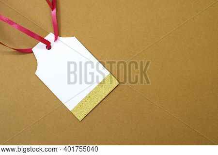 On A Brown Background Is An Empty Price Tag With A Shiny Line And A Red Ribbon.price Tag Gift Tag Sa