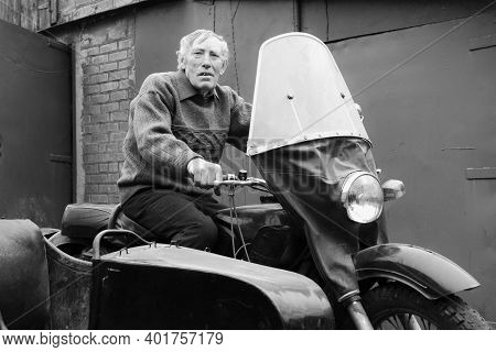 Lyshche, Ukraine - November 15 2012: Elderly Man Posing On An Old Motorcycle With A Sidecar At Rural