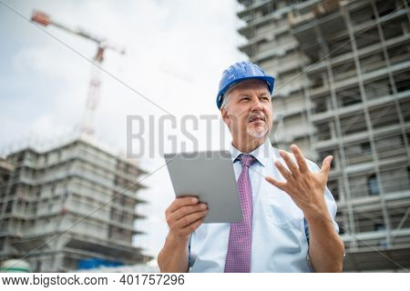 Senior architect site manager using his tablet in front of a construction site