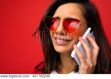 Distraught Girl On A Red Background Speaks On Phone, Close-up.