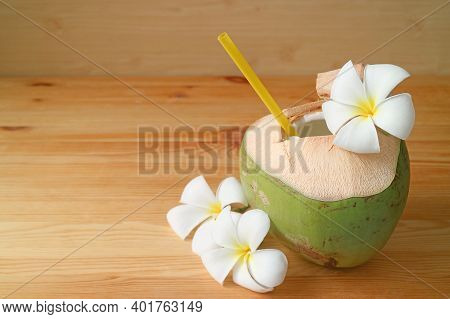 Fresh Young Coconut Juice With Frangipani Flowers On A Wooden Table