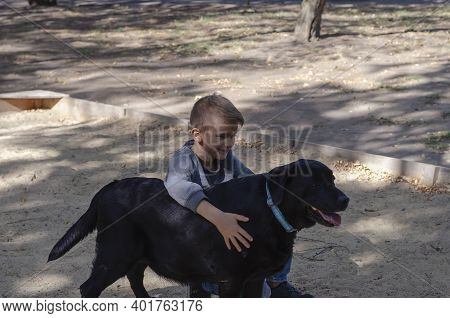 Children And Pets Concept. Happy Child And Dog On A Walk. An Eight-year-old Boy Embraces A Black Lab