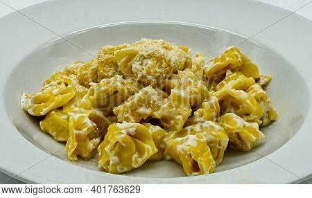 Tortellini Alla Panna With Parmigiano Reggiano Cheese In A White Dish. Traditional Italian Pasta.