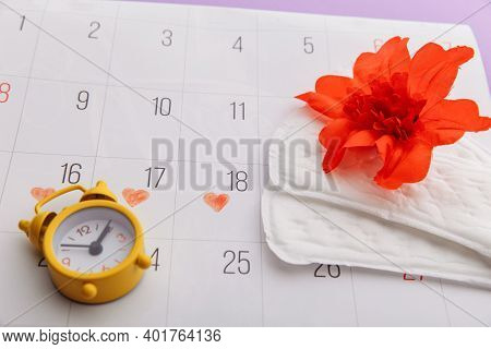 Females Menstrual Cycle And Hygiene Concept. Menstrual Calendar With Sanitary Pads, Alarm Clock And