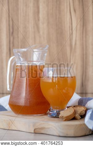 Traditional Russian Cold Rye Drink Kvass In A Glass And A Jug On A Wooden Table. Naturally Fermented