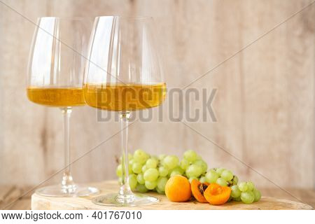 Amber Or White Wine With Fruit. Poured Glass With Wine Surrounded By Grapes, Peaches And Pears On A