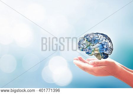 World Mental Health Day Concept: Human Hands Holding Brain Of Earth Over Blurred Blue Nature Backgro