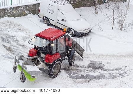 Small Red Wheeled Tractor With Snow Plow In Front And Rotating Sweeper Broom At The Rear In Courtyar