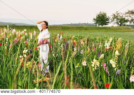 Happy Woman Enjoying Nice Environment Of Flower Farm, Wearing White Clothes, Holding Bouquet Of Glad