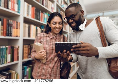 Ethnic Indian Mixed Race Girl And Black Guy In Library. Students Are Using Tablet.