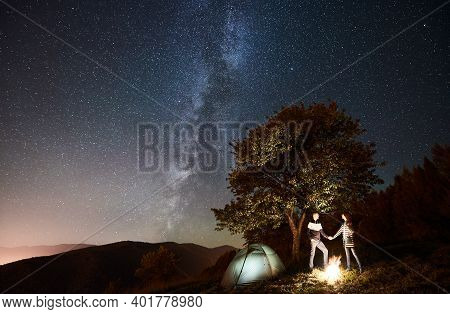 Romantic Couple Hikers Having A Rest At Bonfire Beside Camp And Glowing Tourist Tent, Holding Hands