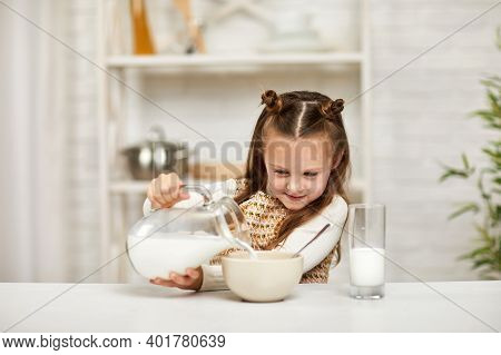 Cute Little Girl Eating Breakfast: Cereal With The Milk. Child Pours Milk Into A Bowl Of Cereal In T