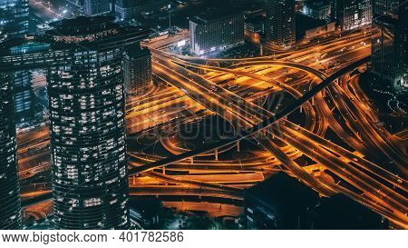 Busy Illuminated Road Intersection At Night Among Modern Futuristic Buildings, Top View.