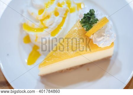 A Piece Of Lemon Cheesecake With Whip Cream On A White Plate