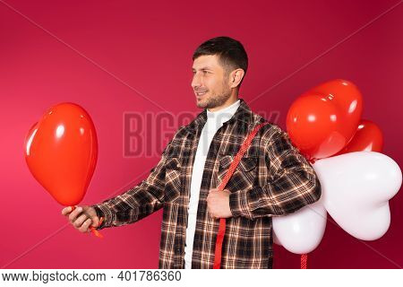 Profile Photo. A Man With Stretches Out A Red Heart Balloon Holding A Bunch Of Balloons On His Shoul