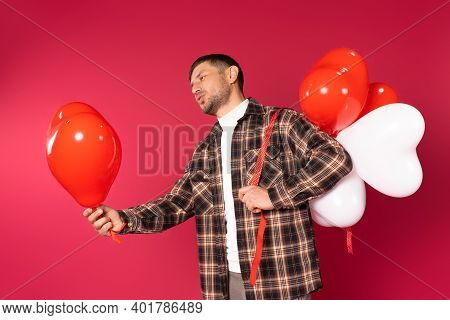A Young Man Holds Out A Red Heart-shaped Balloon And Holds A Bunch Of White And Red Balloons Behind