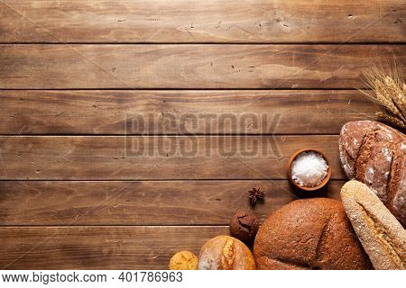 Loaf of fresh bread and buns on wooden table. Assortment of bakery food at wood plank board background texture with copy space. Flat lay top view