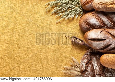 Loaf of fresh bread and buns on table. Assortment of bakery food at linen burap sack rustic cloth napkin background texture with copy space. Flat lay top view