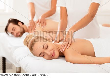Couples Massage. Relaxed Girlfriend And Boyfriend Enjoying Relaxing Neck And Back Massage Lying On B