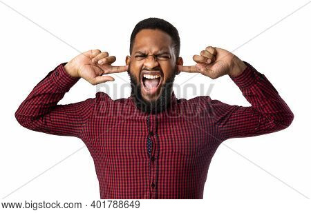 Mad Black Man Shouting Covering Ears With Hands And Closing Eyes Posing Over White Background In Stu