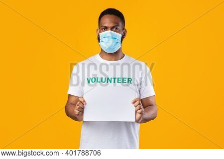 African American Volunteer Guy In Face Mask Holding Blank Paper Poster Advertising Your Text Standin