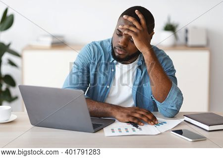 Lack Of Inspiration. Stressed Black Freelancer Guy Sitting At Desk With Laptop And Touching Head In