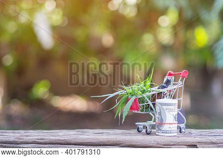 Shopping Trolley With Cannabis Leaves And Cannabis Oil Extracts In A Jar Placed On A Wooden Table An