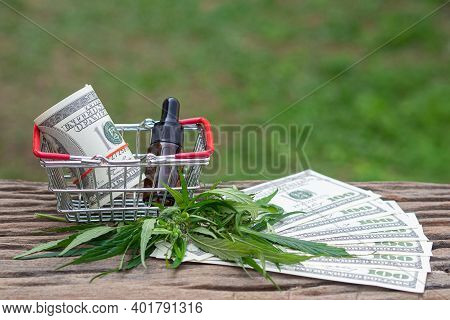 Roll Of Us Dollars And Cannabis Oil Extracts In A Jar Placed On The Shopping Cart With Cannabis Leav