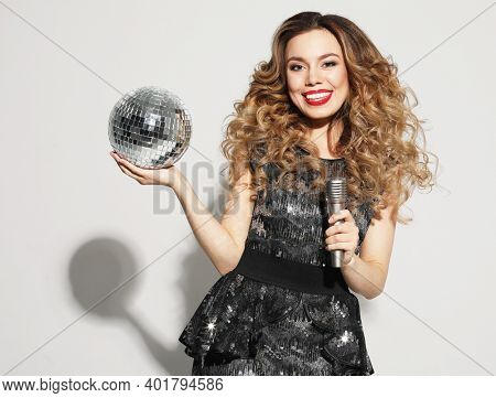 Party, holiday and celebration concept: Young blond woman with long curly hair dressed in evening dress holding a microphone and disco ball, singing and smiling