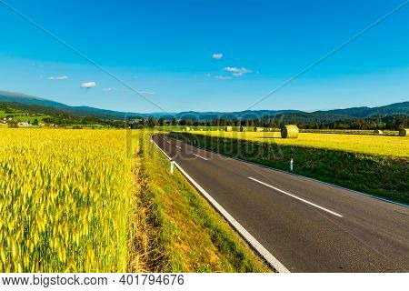 An Empty Road Between Agricultural Fields Leading To The Mountains. Austrian Rural Landscape