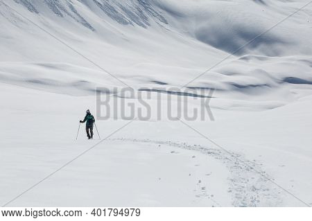 One Women With Snowshoes In Untouched Snowy Winter Landscape In Switzerland