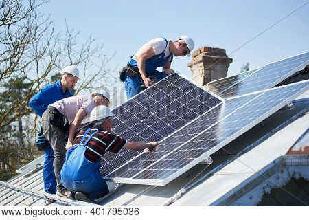 Male Workers Installing Solar Photovoltaic Panel System. Group Of Electricians Mounting Blue Solar M