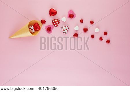 Valentines Day Card With Candy Hearts Flying Out Of An Ice Cream Cone On A Pink Background. Top View