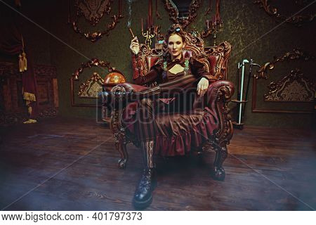 Science fiction, adventures. Beautiful steampunk woman sits in an armchair in a room with vintage victorian interior.