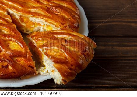Homemade Pie On A Plate And A Sliced ​​piece Of Pie. Freshly Baked Pie On A Wooden Table. Cook At Ho