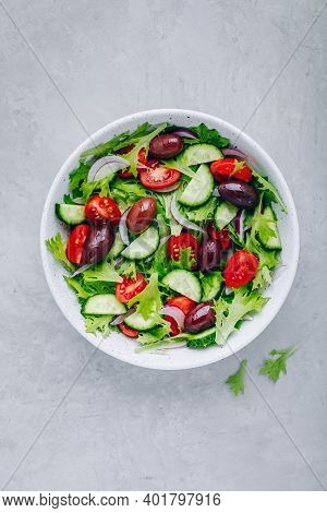 Healthy Green Salad With Fresh Tomato, Cucumber, Red Onion, Olives And Lettuce In Bowl