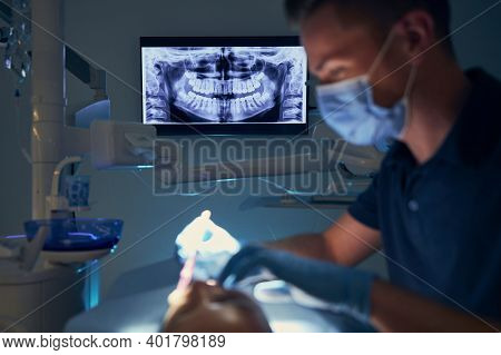 Dentist Examining Patient With Dental Equipments Against Modern Dental Surgery With X-ray.