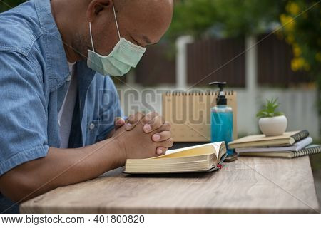 Prayer And Bible Concept. Asian Senior Man Wear Medical Mask Praying, Hope For Peace The World And F