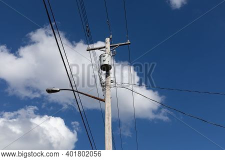Light Wood Power Pole With Transformer And Street Light Before A Deep Blue Sky With White Puffy Clou