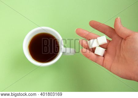 Black Coffee In A White Cup And The Hand Is Holding A Sugar Cube Isolated On A Green Background. Top