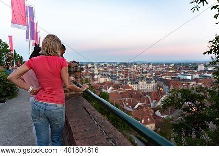 Graz, Austria 19.05.2017 Girl Standing At Schlossberg Mountain, Watching City Panorama.