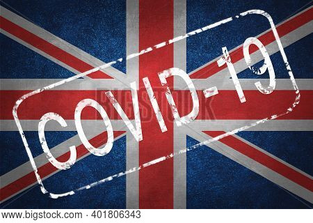 The Stamp Covid-19 On The Background Of The British Flag. Quarantine During The Covid-19 Coronavirus